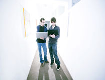 Young business men. Two young business men with laptops discuss on corridor stock image