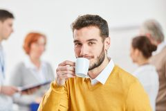 Business man drinking coffee. Young business men drinking coffee in start-up meeting break royalty free stock image