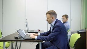 Young business men in lounge suits with laptops are sitting on green chair behind black desk in classroom. One. Spectacled man with beard in the background is stock footage
