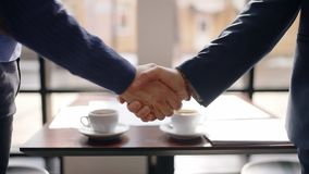 Young business men are shaking hands, say hello, standing at table in restaurant, collaborating people meet for working. Process, fresh coffee is on desk by stock footage