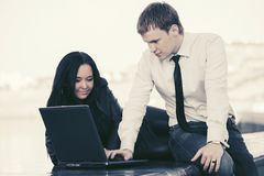 Young business couple using laptop outdoor. Young business men and women using laptop outdoor Stock Photo