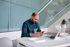 Young business owner reading text message on mobile phone after development report on net-book while sitting in office interior, Stock Photo