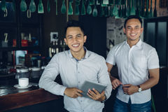 Young business owner and team partner with tablet in cafe Stock Images