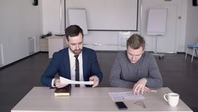 Young business partners are discussing blueprint at table in large company. Two men are at meeting sitting at desk in modern office. Successful businessmen met stock video