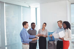 Young business partners discussing at office. Young business partners discussing while standing at office Stock Images