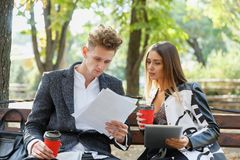 Young business partners look through their documents and sit on a bench in the street. stock photo