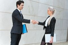 Young buisness couple shaking hands over deal. Young business partners shaking hands over deal outdoors Royalty Free Stock Photos