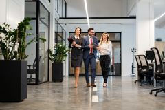 Business partners walking down in office building and discussing work Royalty Free Stock Photo