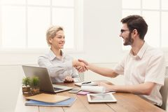 Agreement of young business partners in office. Young business partners work in modern office. Shake hands as a sign of good deal, success and agreement concept Royalty Free Stock Image