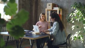 Young business partners are working with laptop and talking. Dark-haired woman is typing, blonde is suggesting ideas. Young female business partners are working stock video