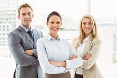 Young business people with arms crossed in office Royalty Free Stock Image