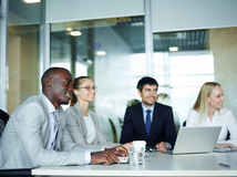 Young Business People in Briefing Meeting. International group of young enthusiastic business people smiling sitting round meeting table in conference room of royalty free stock photo