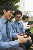 Young business people checking their cell phones Royalty Free Stock Photos