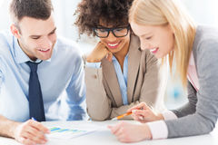 Young business people discussing in office. Smiling Royalty Free Stock Photography