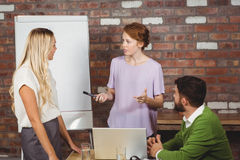 Young business people discussing during presentation Royalty Free Stock Images