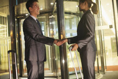 Young business people handshaking outside of the office Royalty Free Stock Photo