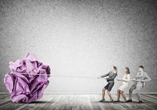 Young business people and huge paper ball as symbol of creativity Royalty Free Stock Images