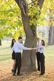Young Business People Hugging Tree Royalty Free Stock Image