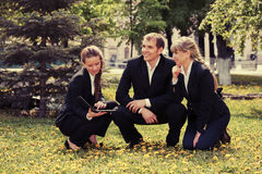 Young business people with laptop in city park Stock Images