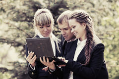 Young business people with laptop in city park Royalty Free Stock Photography