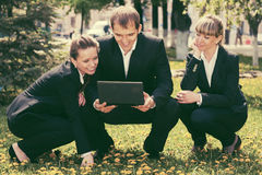Young business people with laptop in city park Royalty Free Stock Image