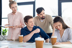 Young business people looking at colleague on small business meeting Royalty Free Stock Images