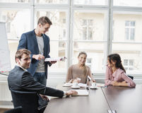 Young business people looking at laptop in meeting Royalty Free Stock Photos