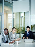 Young Business People in Meeting. International group of modern young business people sitting at meeting table in conference room of modern office listening to Stock Image