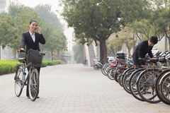Young business people parking their bicycles and talking on the phone on the sidewalk in Beijing, China Royalty Free Stock Photos
