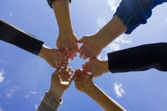 Young business people putting their hands together, Sky backgrou. Nd, Stack of hands. Unity and teamwork concept Royalty Free Stock Photos