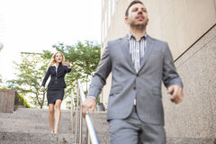 Young business people running downstairs Stock Image