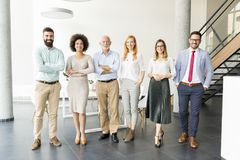 Young business people with senior colleague. Standing in the office Royalty Free Stock Photography