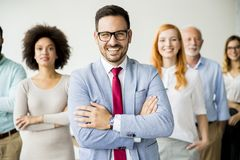 Young business people with senior colleague. Standing in the office Royalty Free Stock Photos