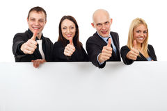 Young business people showing thumbs up and banner Royalty Free Stock Photos
