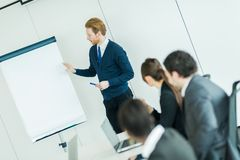 Young business people sitting at a conference table and learning Stock Photos