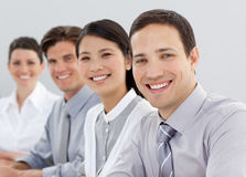 Young business people sitting in a line Royalty Free Stock Images