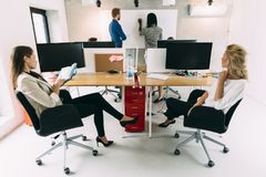 Business people sitting in office and learning new technologies. Young business people sitting in office while listening to the lecturer and learning new Royalty Free Stock Image