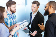 Young business people standing and talking with chief executive Royalty Free Stock Image