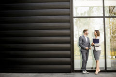 Young business people talking and viewing documents outdoor. Young business people talking and viewing documents royalty free stock image