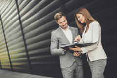 Young business people talking and viewing documents outdoor. Young business people talking and viewing documents stock photo