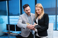 Young business people talking and viewing documents Royalty Free Stock Photography