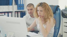 Young business people using computer in the office. Two colleagues have a discussion while working together and looking at pc monitor stock footage