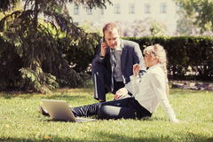 Young business people using laptop in city park Stock Images