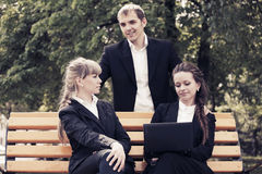 Young business people using laptop in a city park Stock Photography