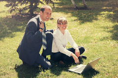 Young business people using laptop in city park Royalty Free Stock Photo