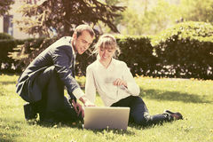 Young business people using laptop in city park Stock Photo
