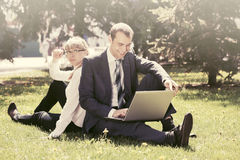 Young business people using laptop in city park Royalty Free Stock Photos