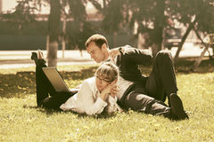 Young business people using laptop in a city park. Young business people using laptop lying on grass in city park Stock Photo