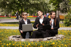 Young business people using laptop in a city park Royalty Free Stock Images