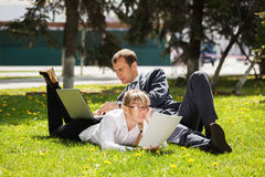 Young business people using laptop in a city park Royalty Free Stock Photography